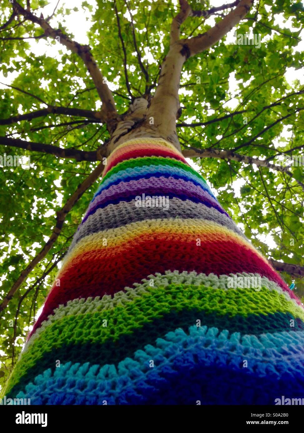 Tree with crochet rainbow on trunk - Stock Image