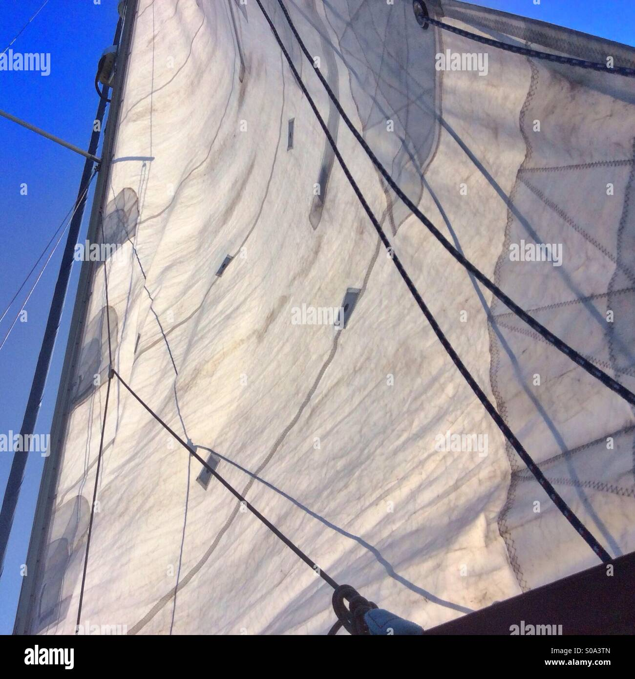 Yacht sail cloth loosely blows in the wind against deep blue sky. - Stock Image