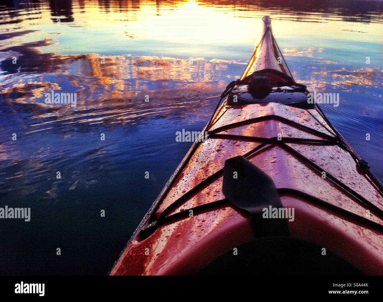 Sunset reflects in the sea water and the bow of red sea kayak Stock Photo