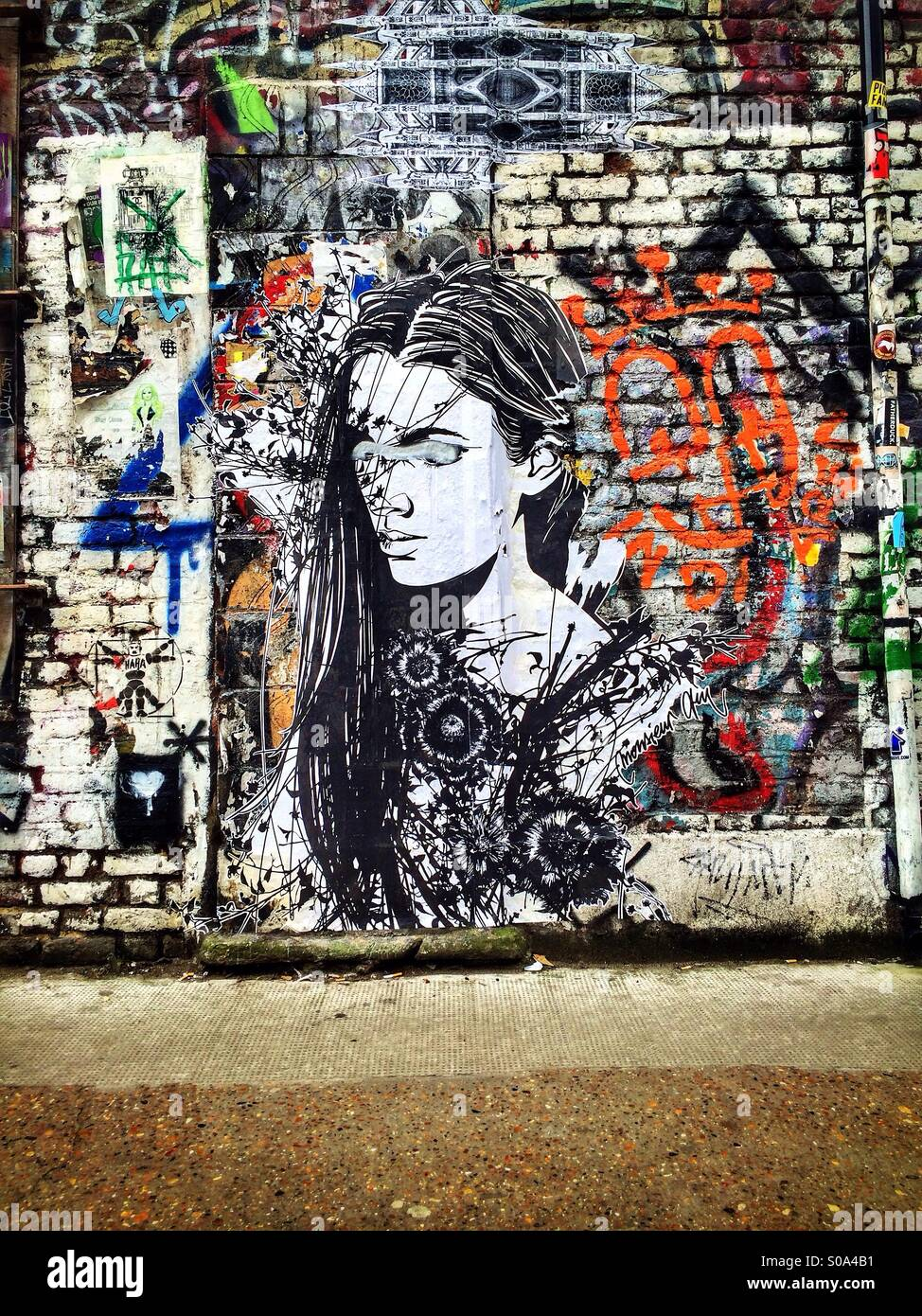 Graffiti paste-up depicting a girl with eyes closed by ...