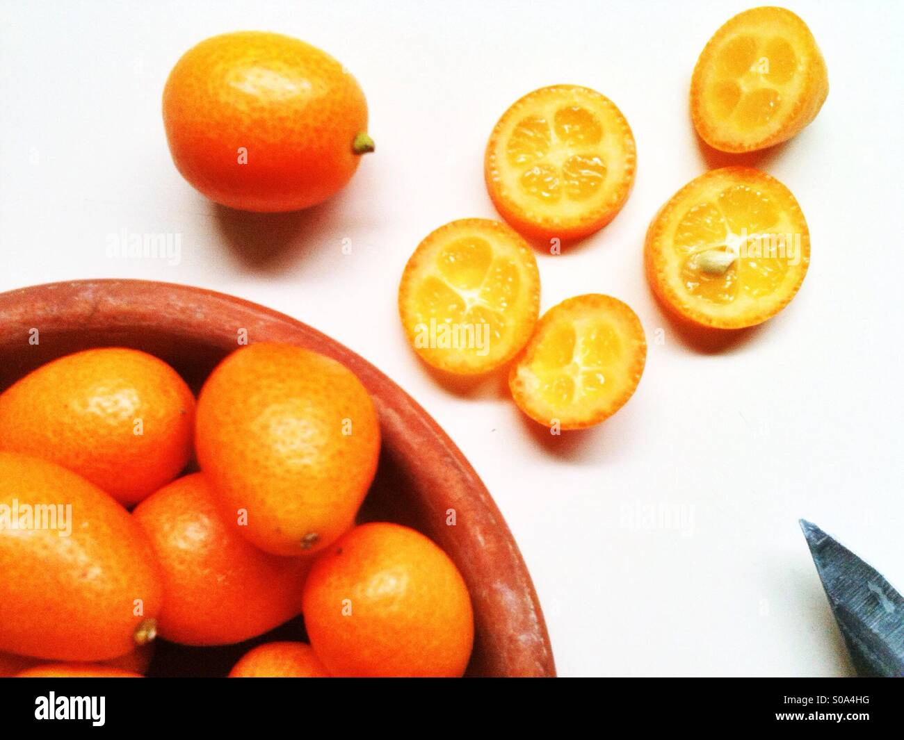 Sliced orange cumquats on a countertop - Stock Image