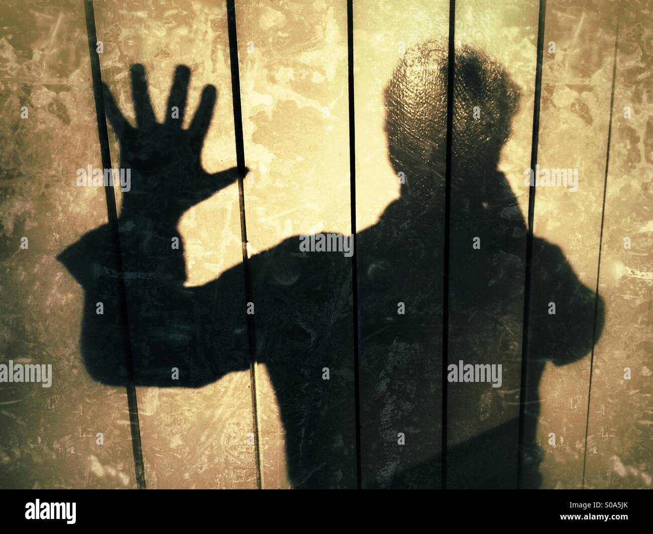 Man casting a shadow on a wall, Expressing, STOP!, no more! Stock Photo