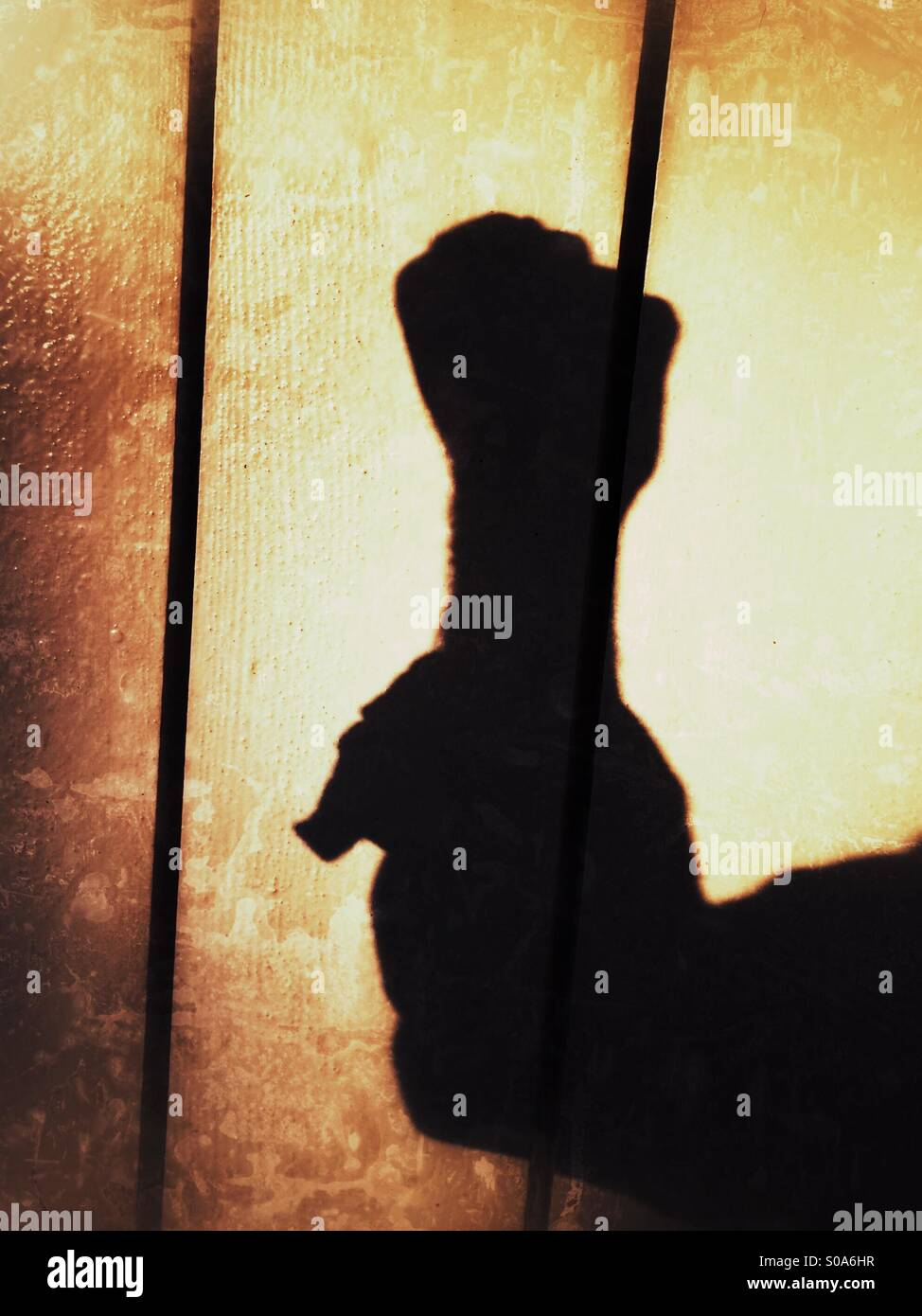 A man casting a shadow on a wall, counting on his hand. Number zero. Stock Photo