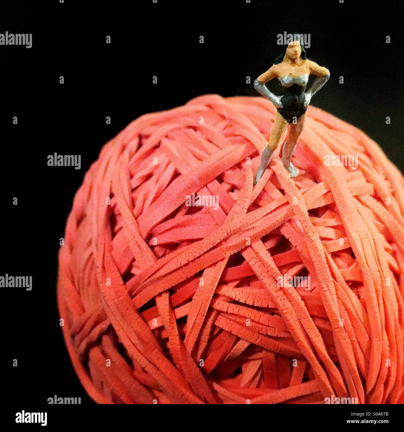 A small figure of a woman dressed like a superhero on top of a large ball made of red rubber bands - Stock Image