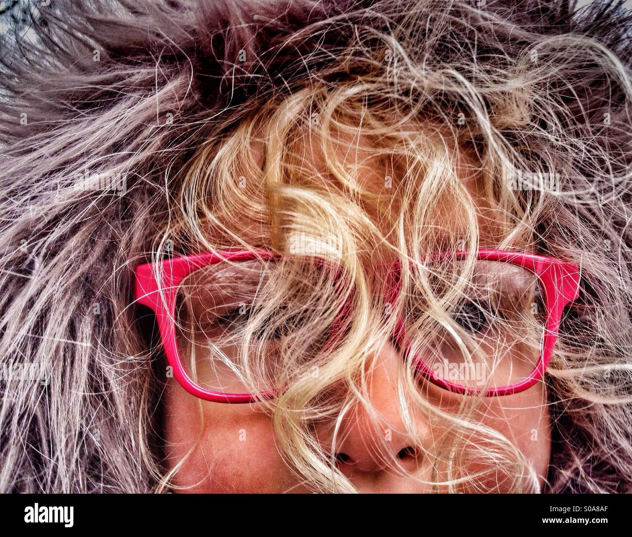 Young Girl wearing furry hood with face obscured by curly blind hair - Stock Image