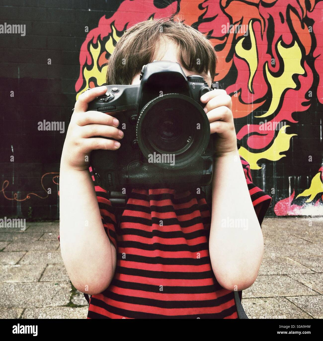 Small boy with big camera. A 5 year old boy using a full size SLR. - Stock Image