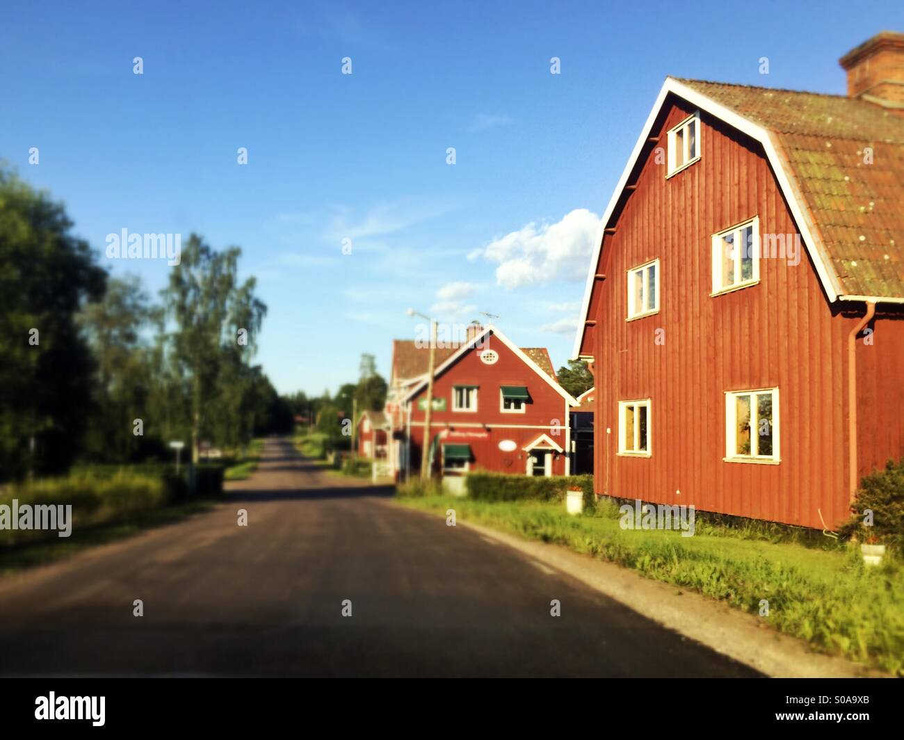 Traditional Falu red houses lining road in Tallberg, Dalarna, Sweden in summer - Stock Image