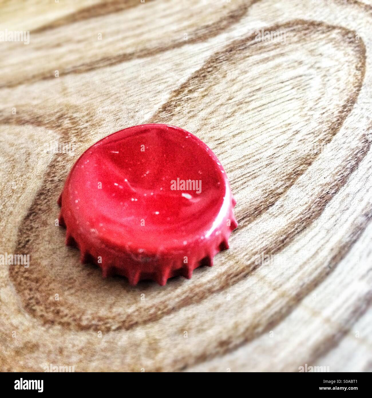 A red bottle top sits on a wooden work top amongst the wood grain pattern. - Stock Image