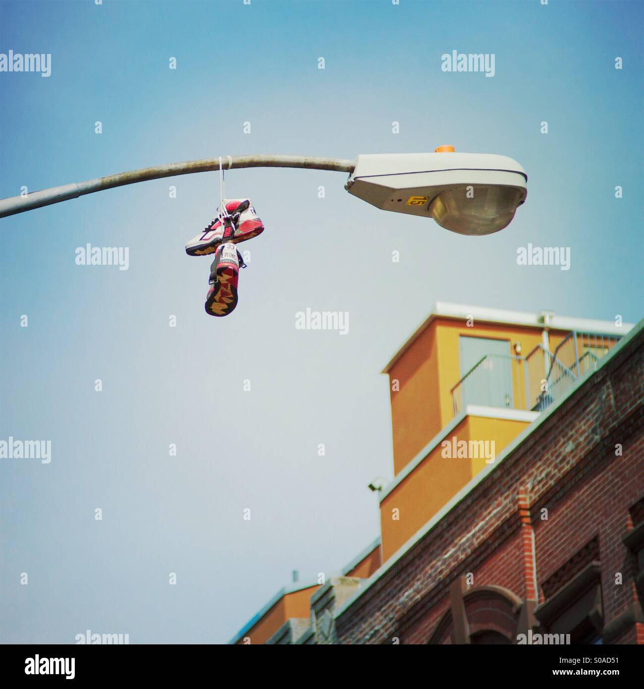 Sneakers hanging from lamp post in Harlem, New York City - Stock Image