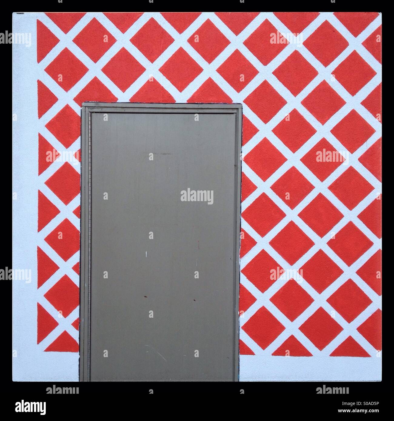 Service door in a wall painted in a red and white criss