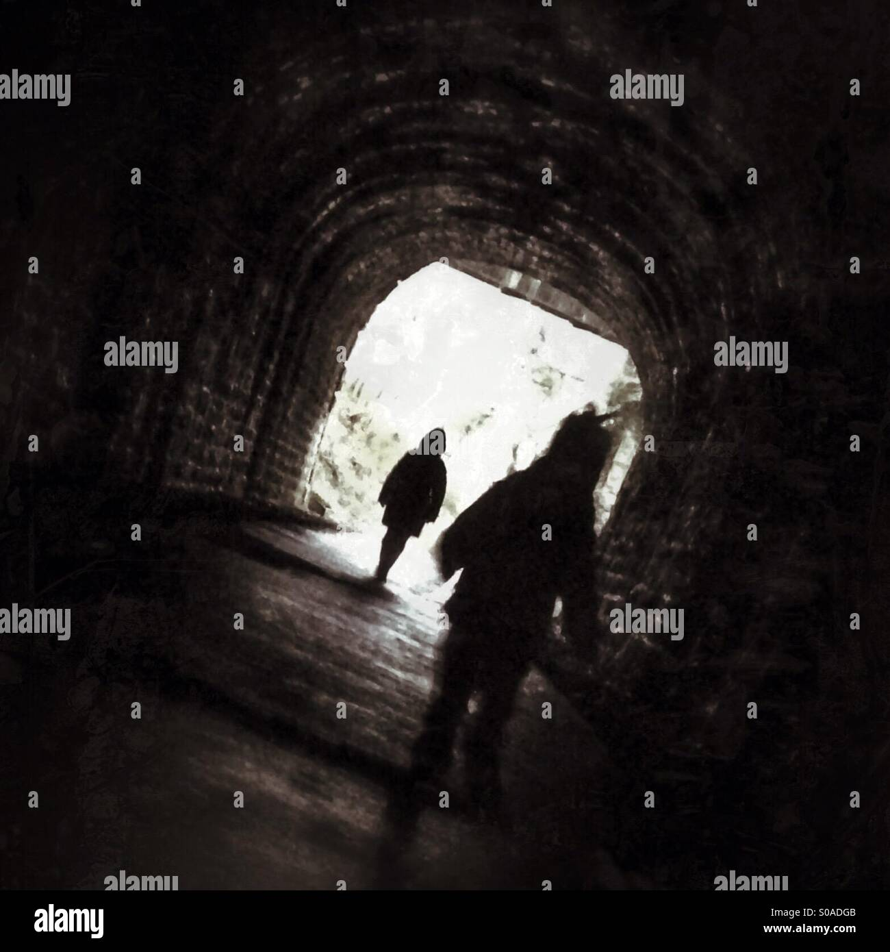 Being followed in a dark tunnel - Stock Image