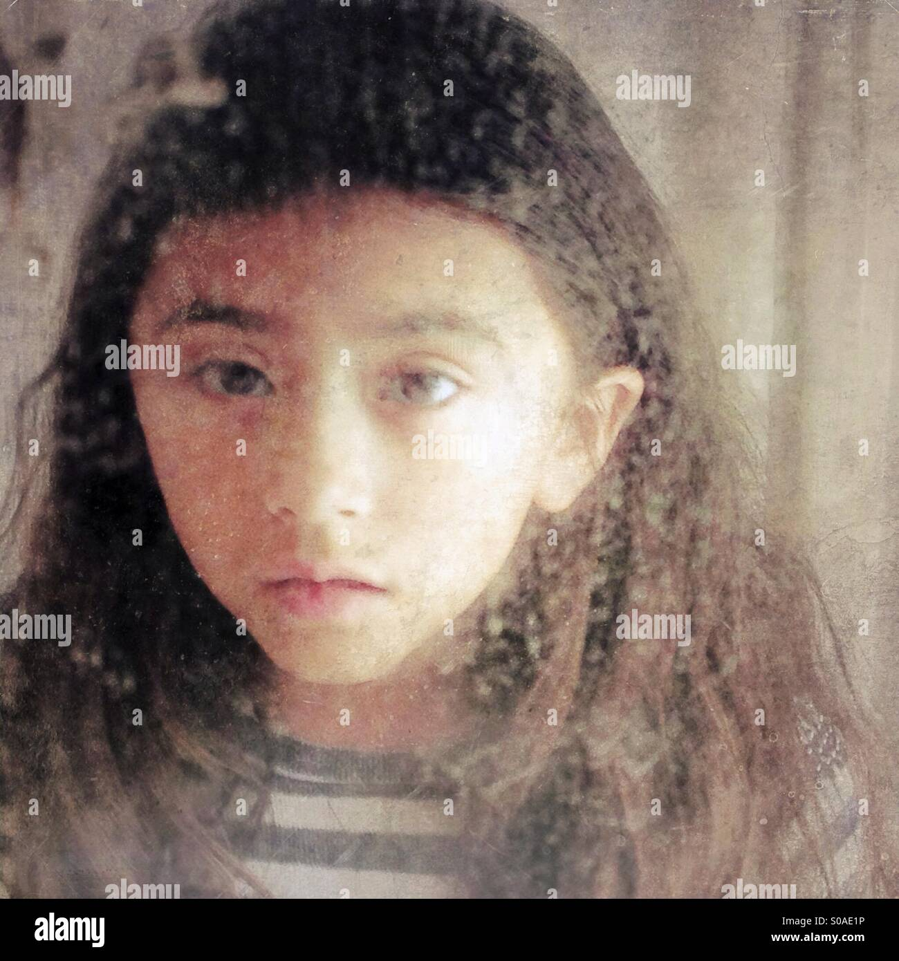 The reflection of a little girl looking into an old mirror looking sad or sick. - Stock Image