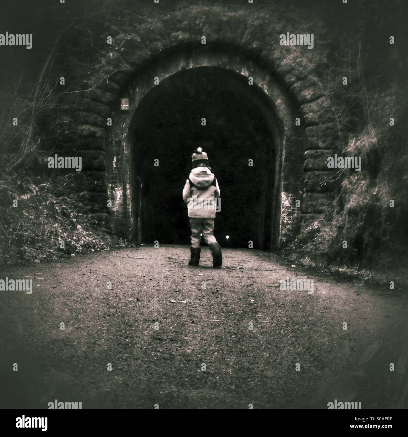 Boy entering tunnel alone - Stock Image