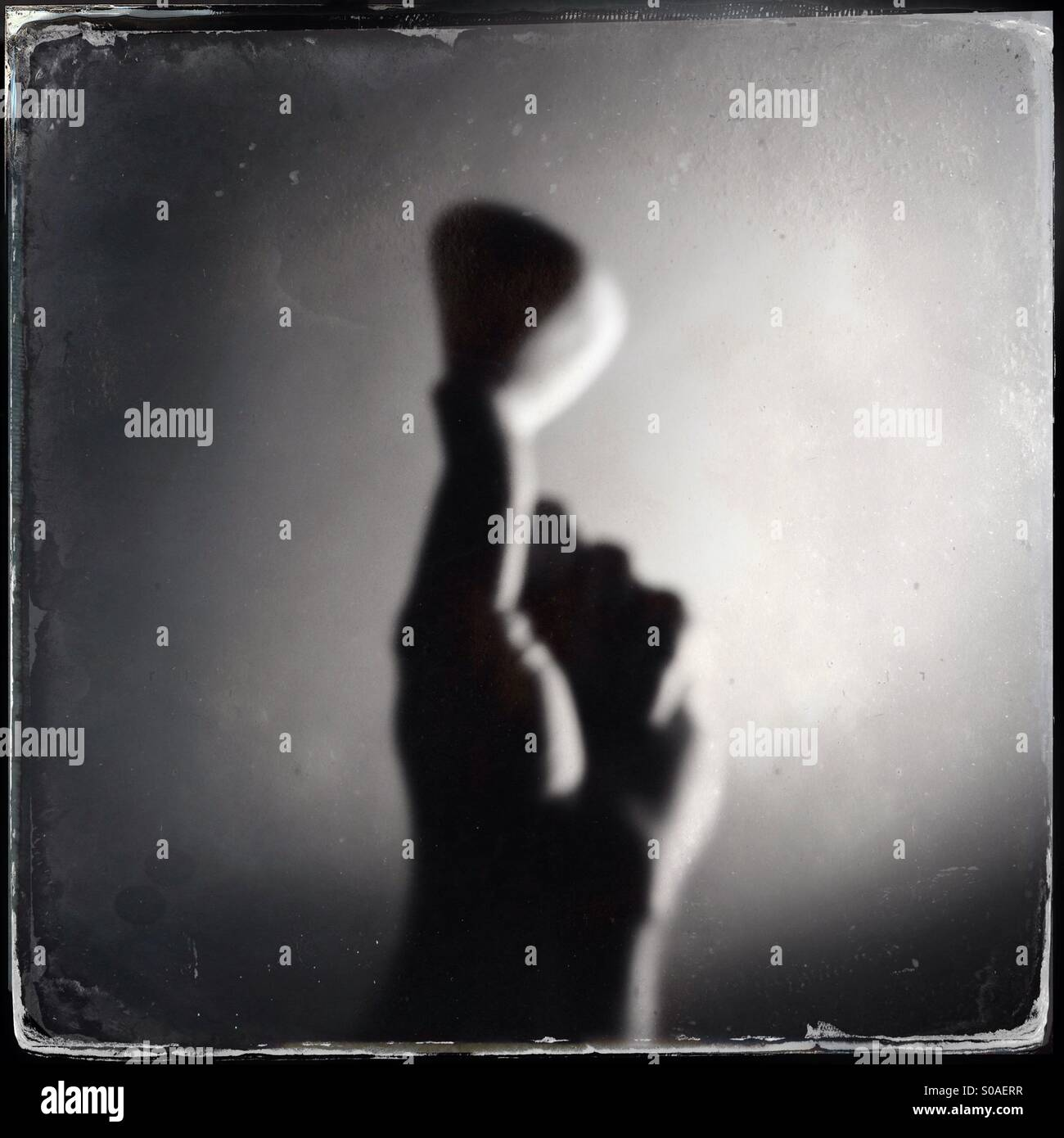 Out if focus image of a hand holding  a heart shaped pebble - Stock Image
