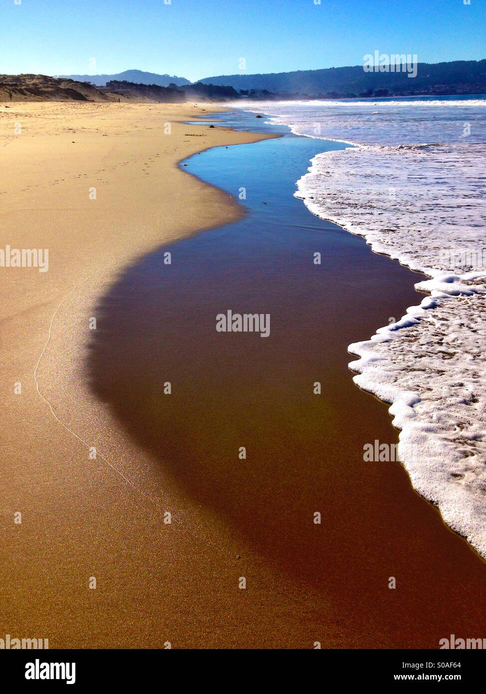 Gentle surf on sandy beach in California - Stock Image