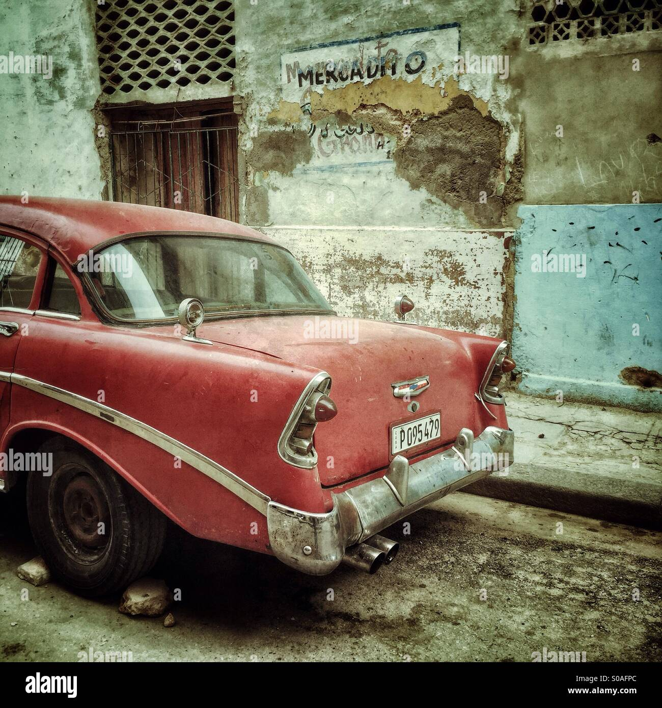 Rear view of a red vintage Cuban Car, parked by a peeling painted decaying exterior wall. Havana, Cuba, Caribbean Stock Photo