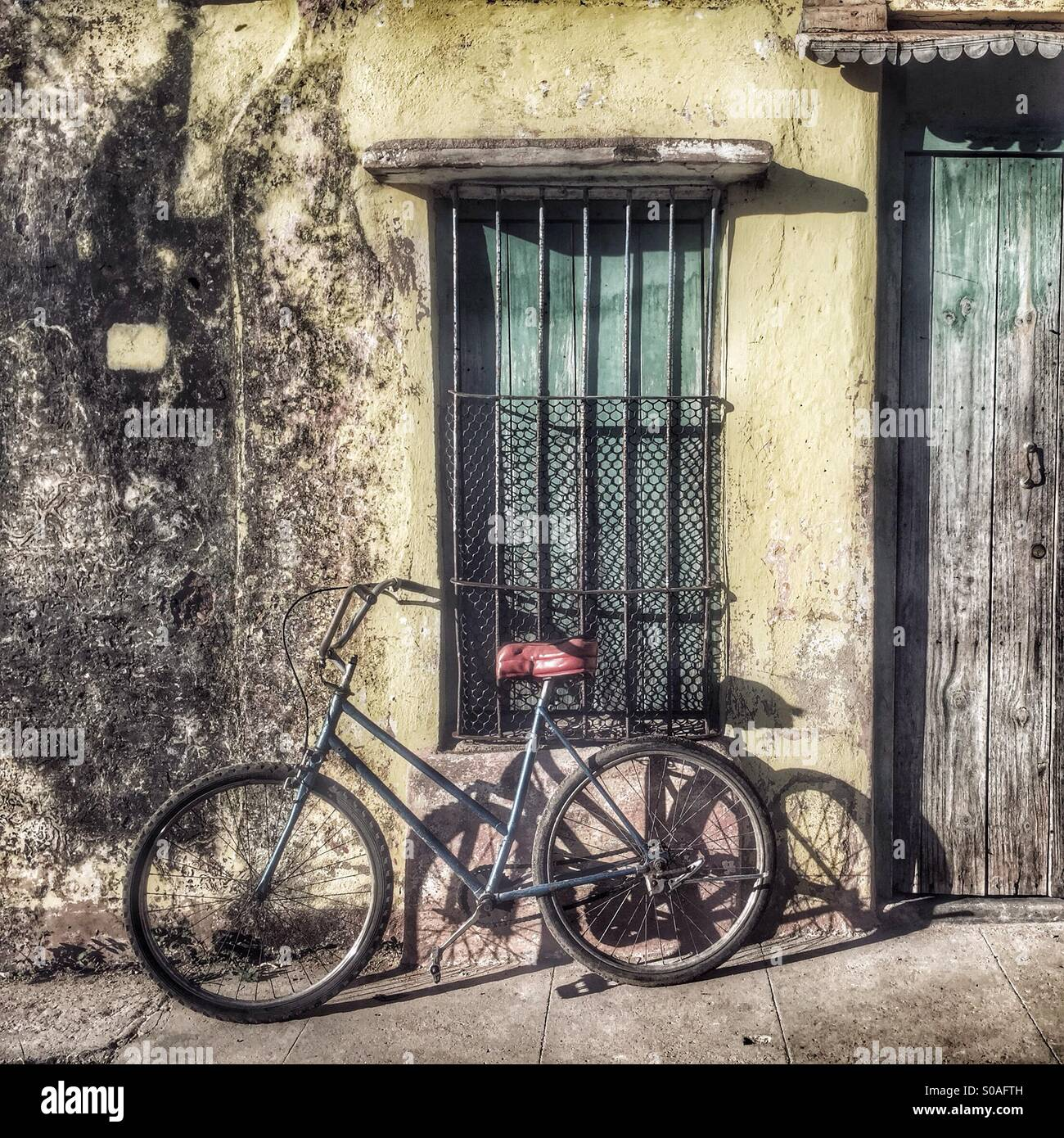 Bicycle leaning and casting a shadow against a grubby shuttered window walled property. Trinidad Sancti Spiritus - Stock Image