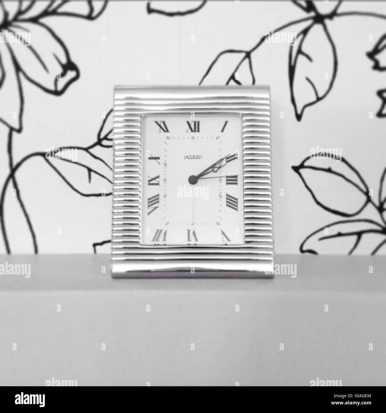A small contemporary mantel clock in a modern living room. - Stock Image