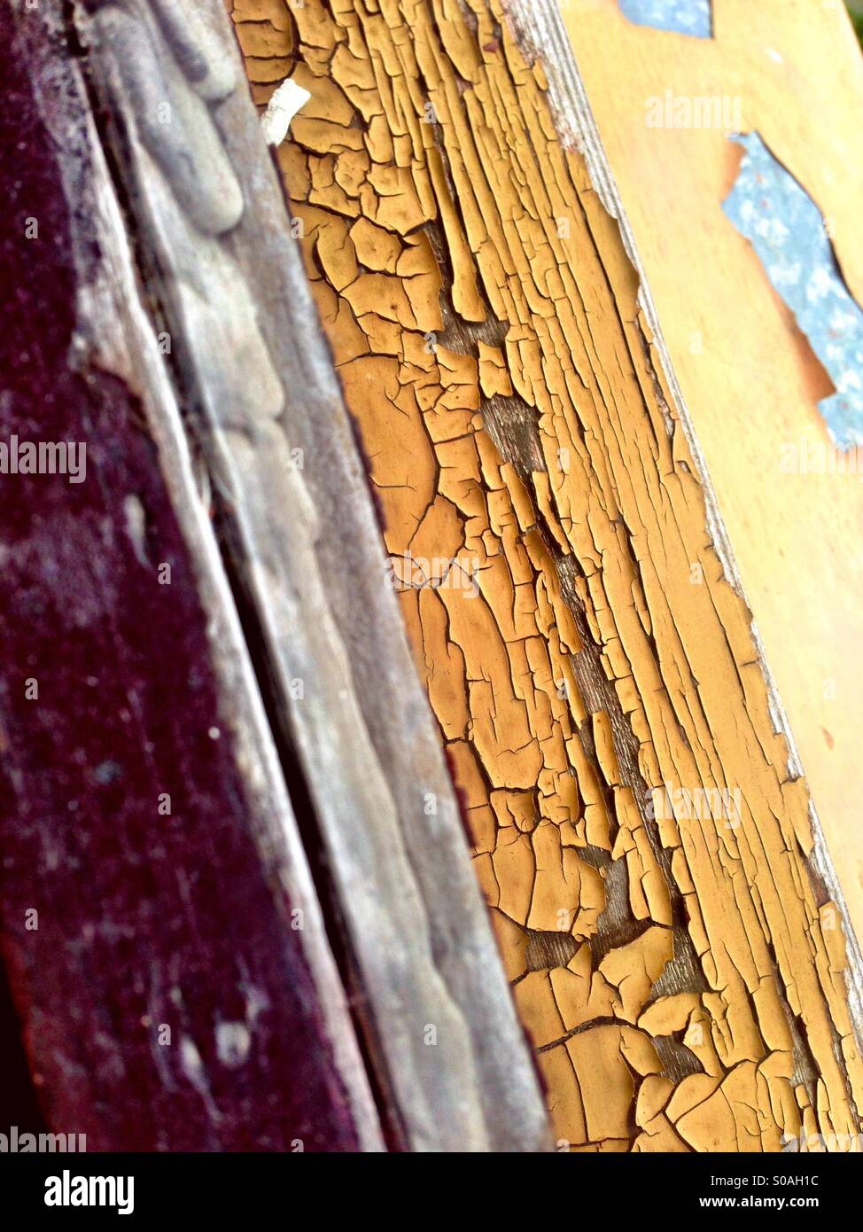 The tell-tale signs of age on a windowpane with chipped and cracking weathered paint Stock Photo