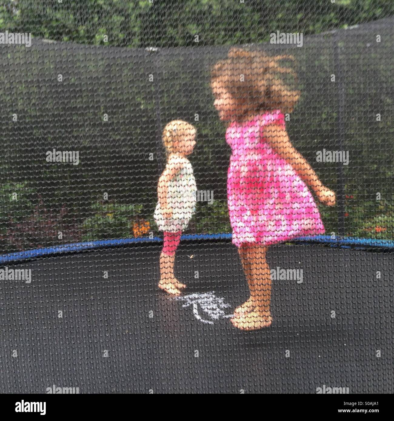 Two little girls jumps on a trampoline. - Stock Image