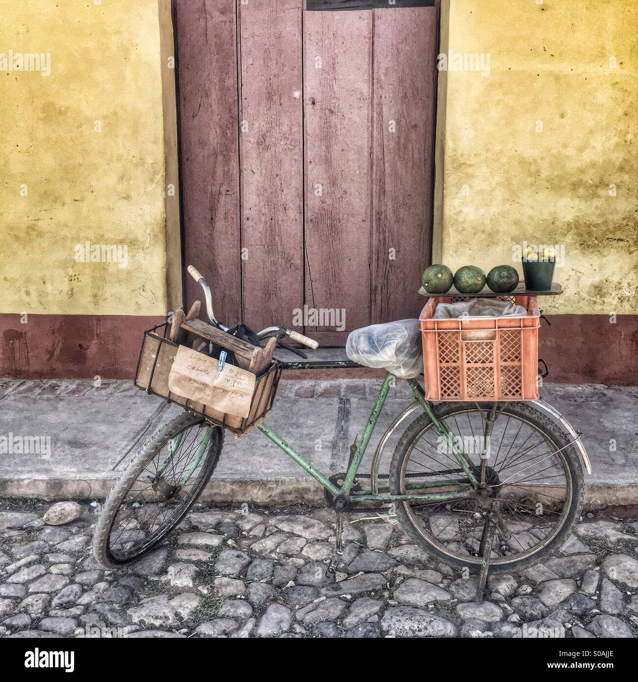 Fruit and vegetable sellers bicycle with produce outside a yellow painted property. Trinidad, Cuba, Caribbean - Stock Image