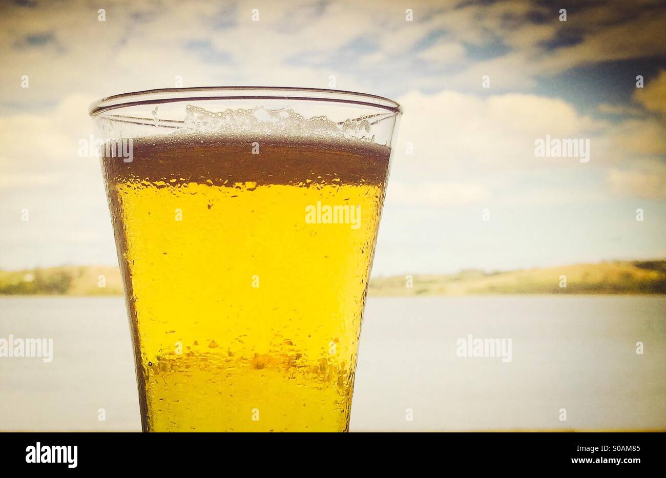 Cold beer on a hot day against summer sky. - Stock Image
