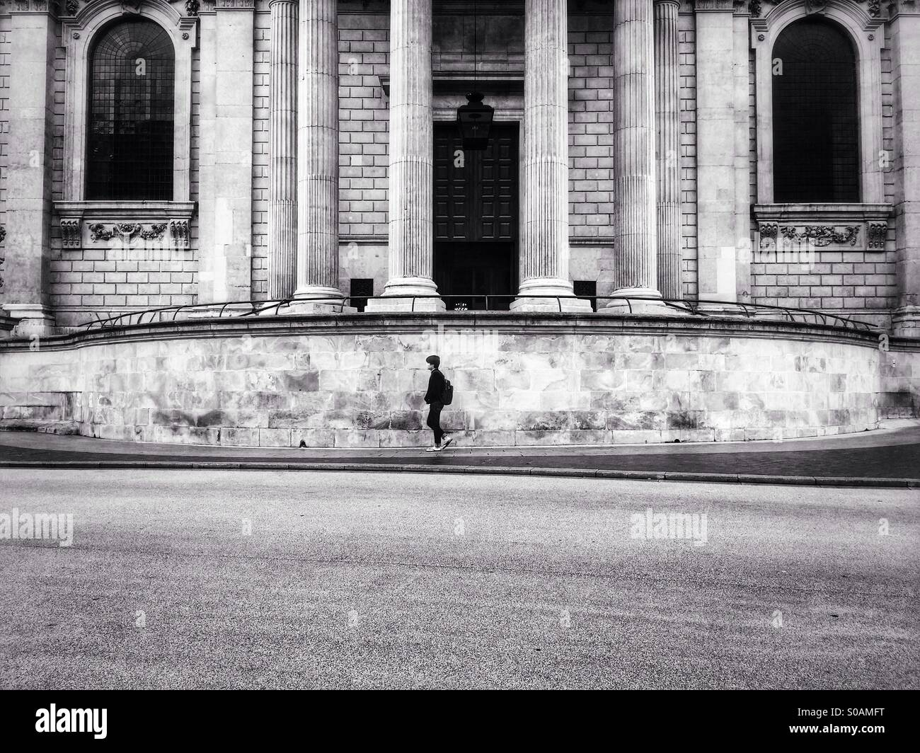 A man dressed in black walks past Saint Paul's Cathedral in London, England, UK. Stock Photo