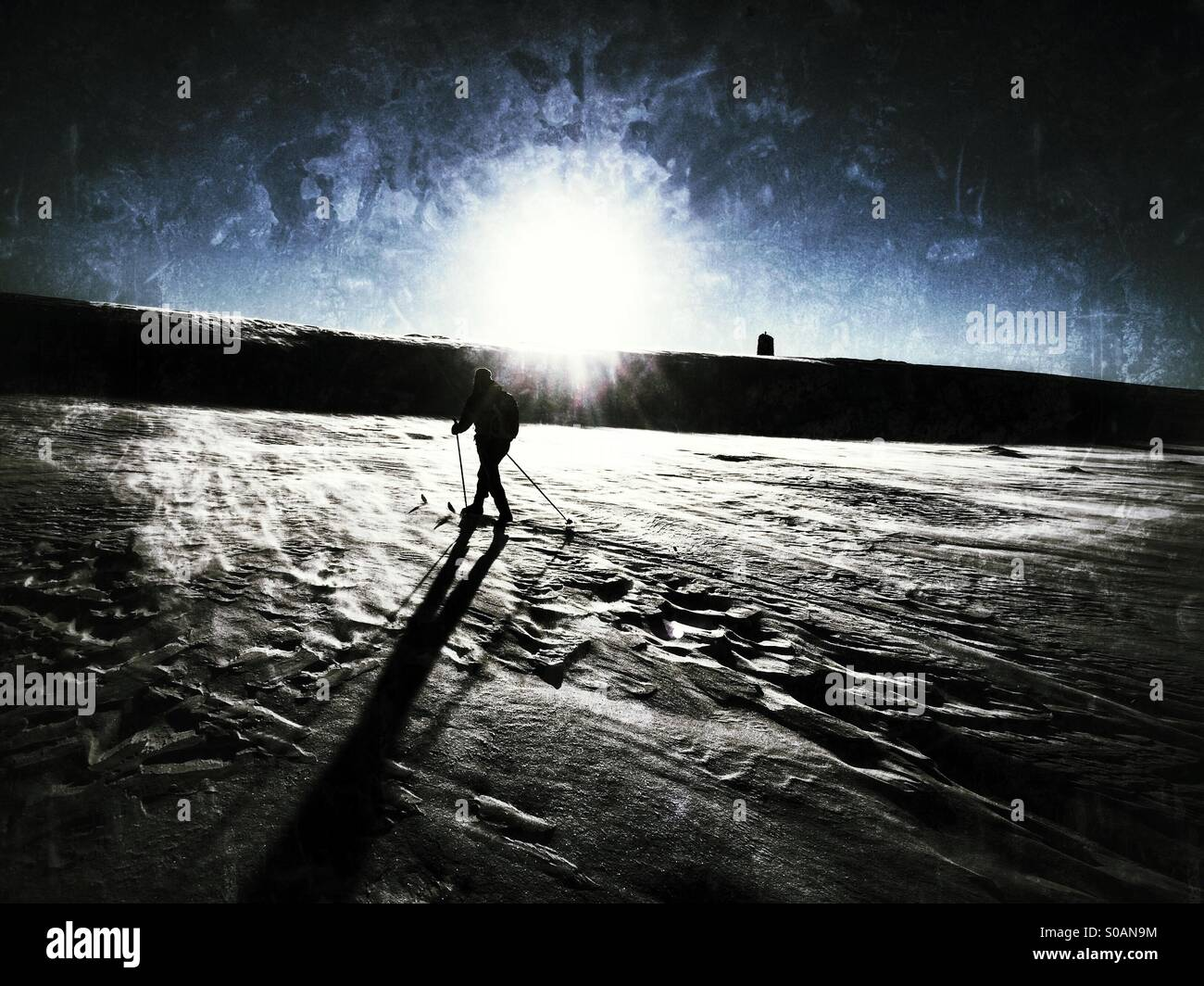 Nordic skier going cross-country skiing into the sun casting a long shadow. Stock Photo