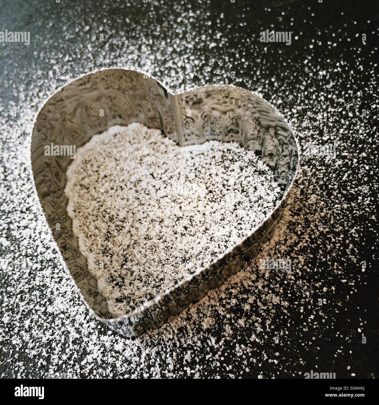 Heart shaped cookie cutter, dusting of icing sugar, black slate board, angled - Stock Image