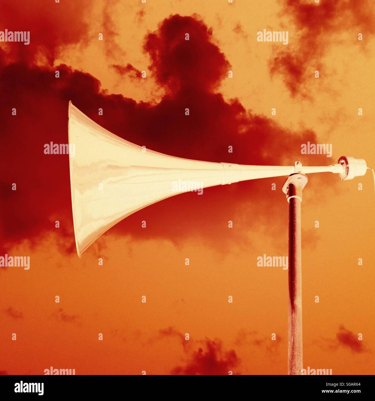 Loudhailer loudhailer outside against colourful sky digitally altered - Stock Image