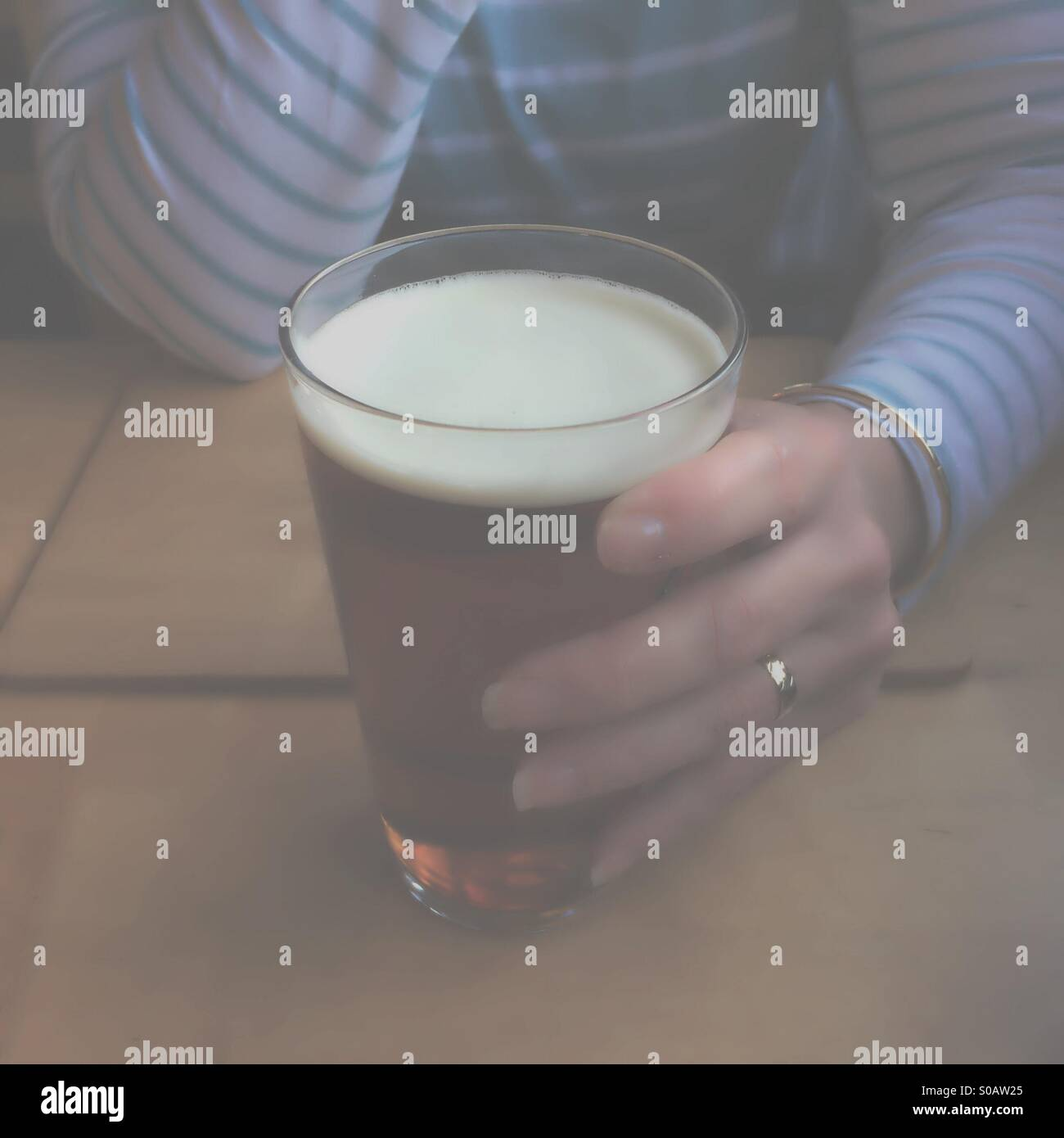Depressing image looking through a fog at woman holding pint of beer in public house - Stock Image