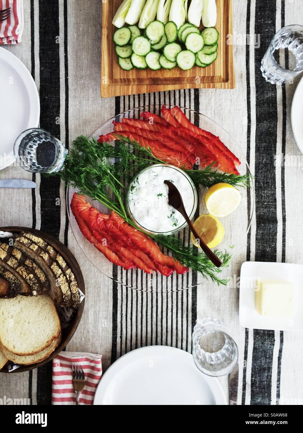 Scandinavian lunch of two-toned home cured gravlax with cucumber yogurt sauce, bread and butter and sliced cucumber - Stock Image