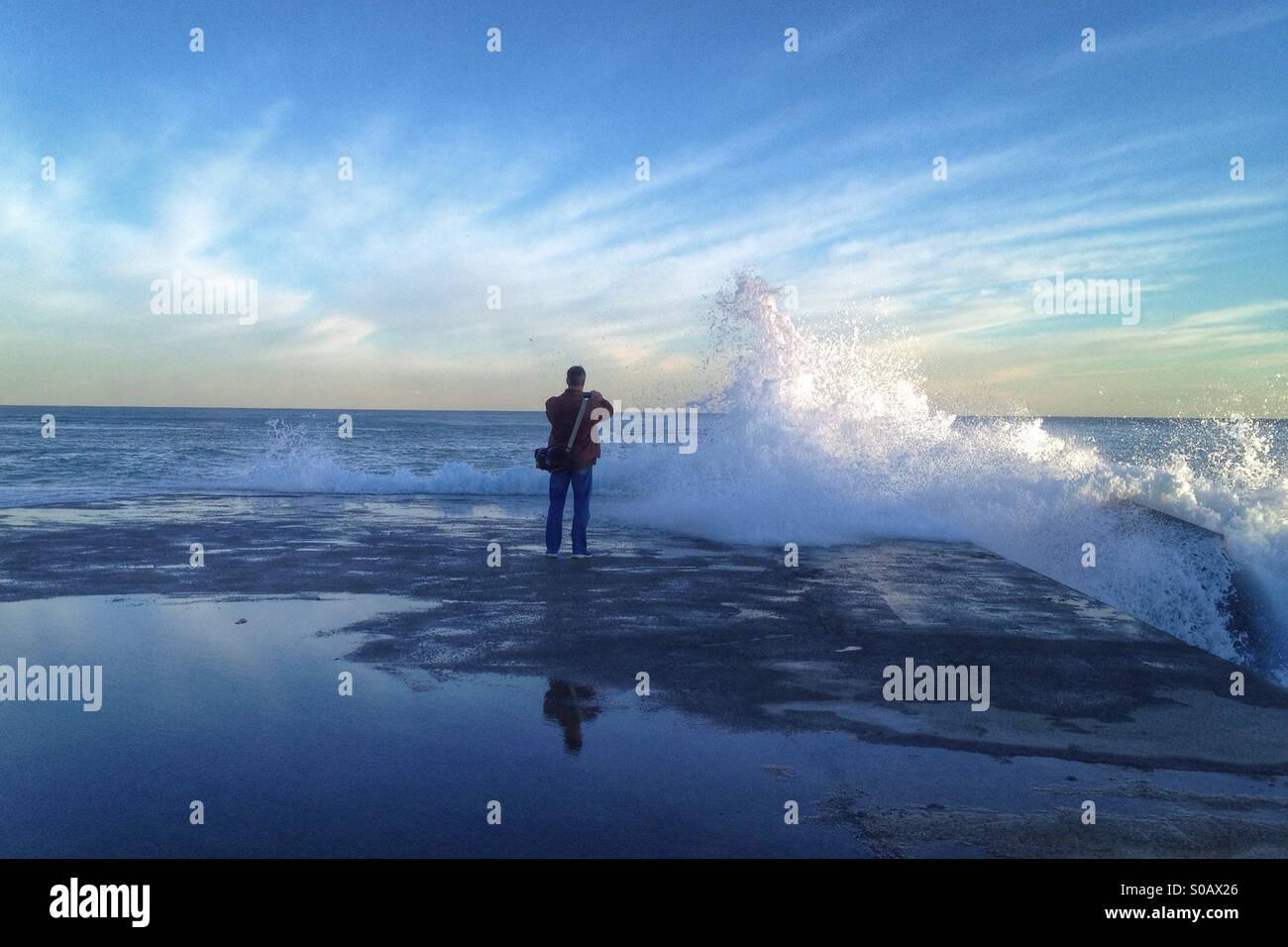 Photographer taking pictures of the wavrd - Stock Image
