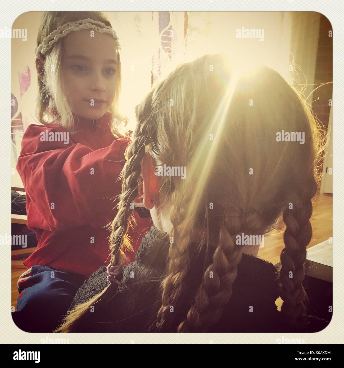 Mother and daughter making plaits in each other's hair in beautiful dreamy sunshine - Stock Image