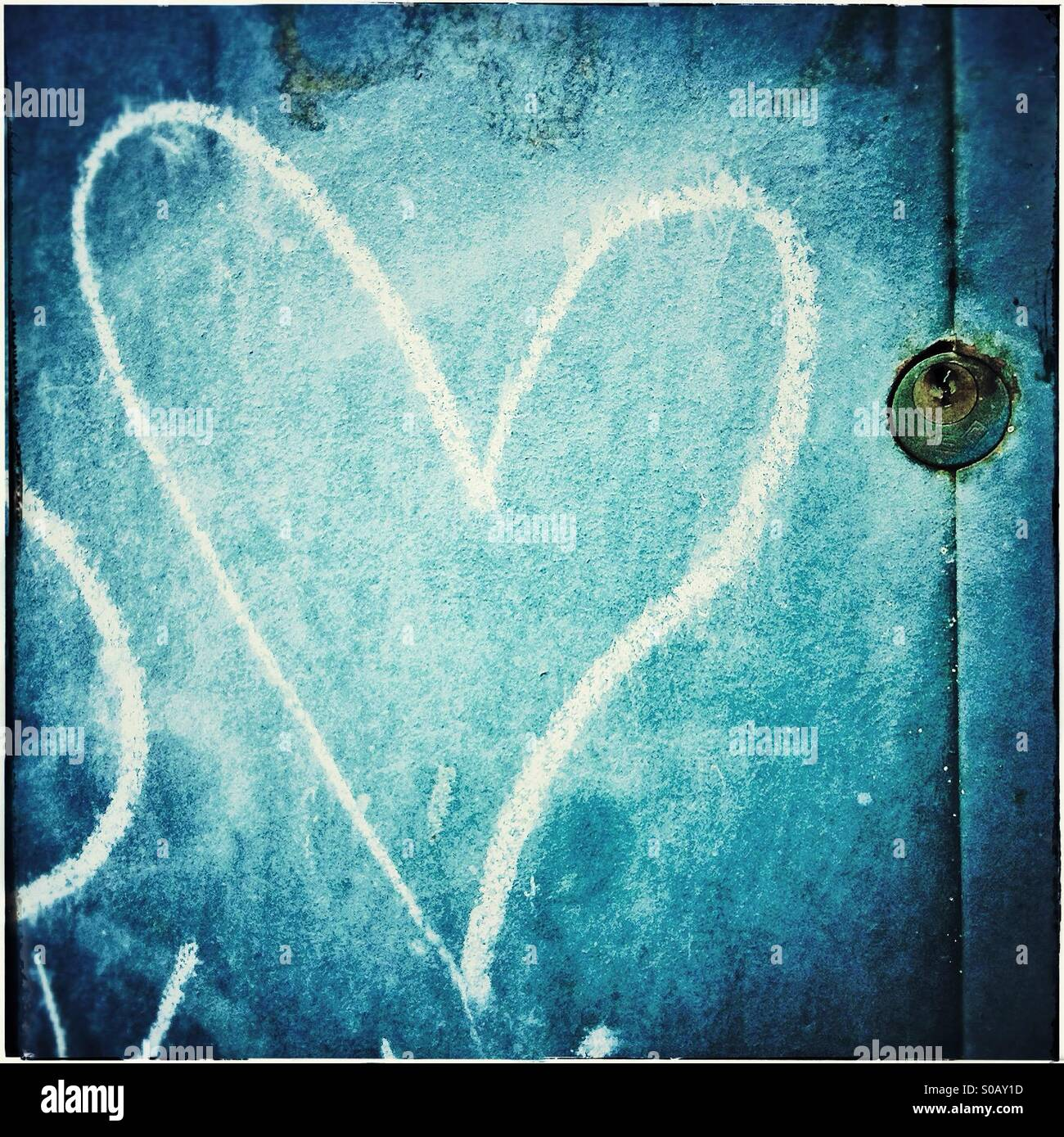A love heart painted in chalk and a padlock in a blue doorStock Photo