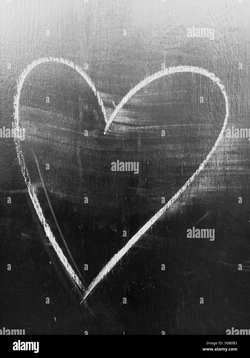 Heart shape graffiti in NYC drawn with chalk and slightly blurred. - Stock Image
