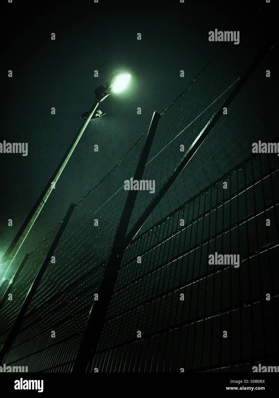 Metal fence and lights at night - Stock Image