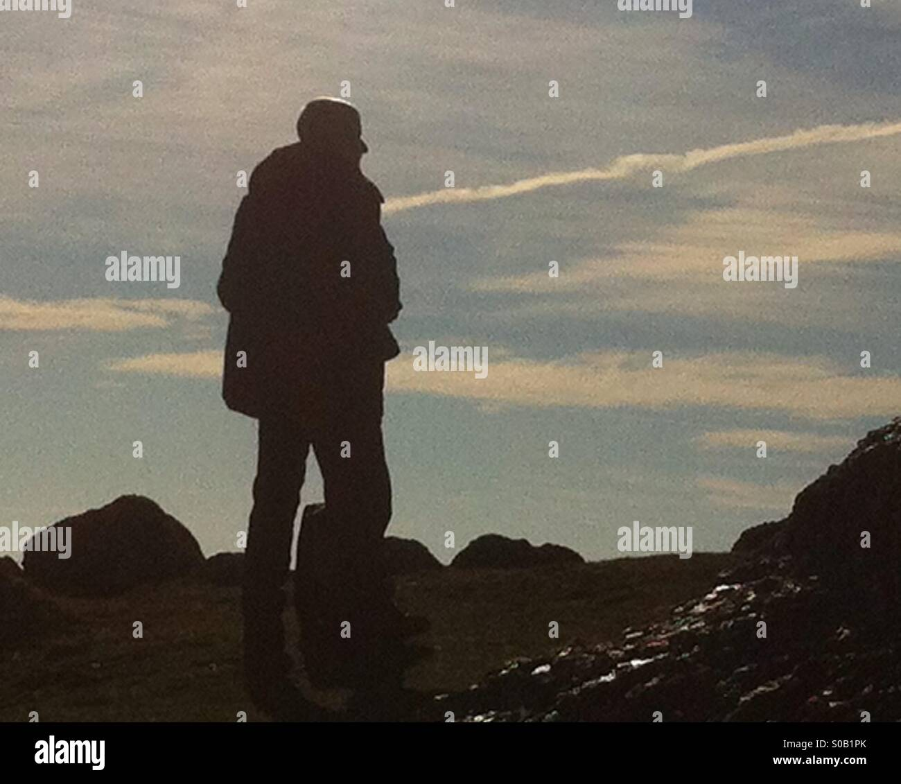 Man standing on rock overlooking Rhossili beach in the Gower peninsula - Stock Image