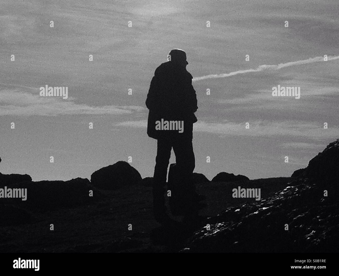 Silhouette of a man standing on rock overlooking Rhossili beach in the Gower peninsula Stock Photo