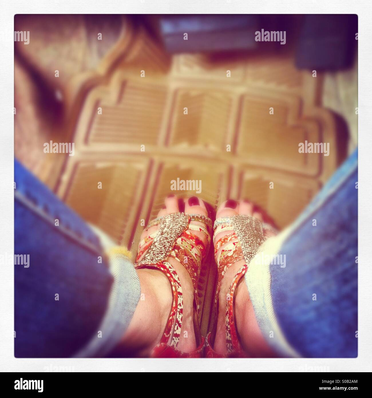 Looking down on blue jeans and painted red toes in ethnic beaded sandals on top of beige plastic Matt in a car. Stock Photo