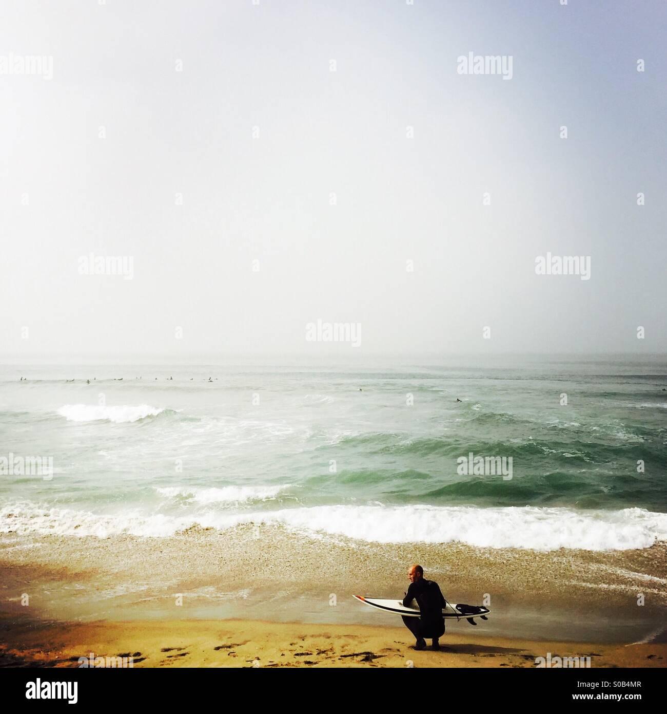 A surfer waits on the beach. Manhattan Beach, California USA.Stock Photo
