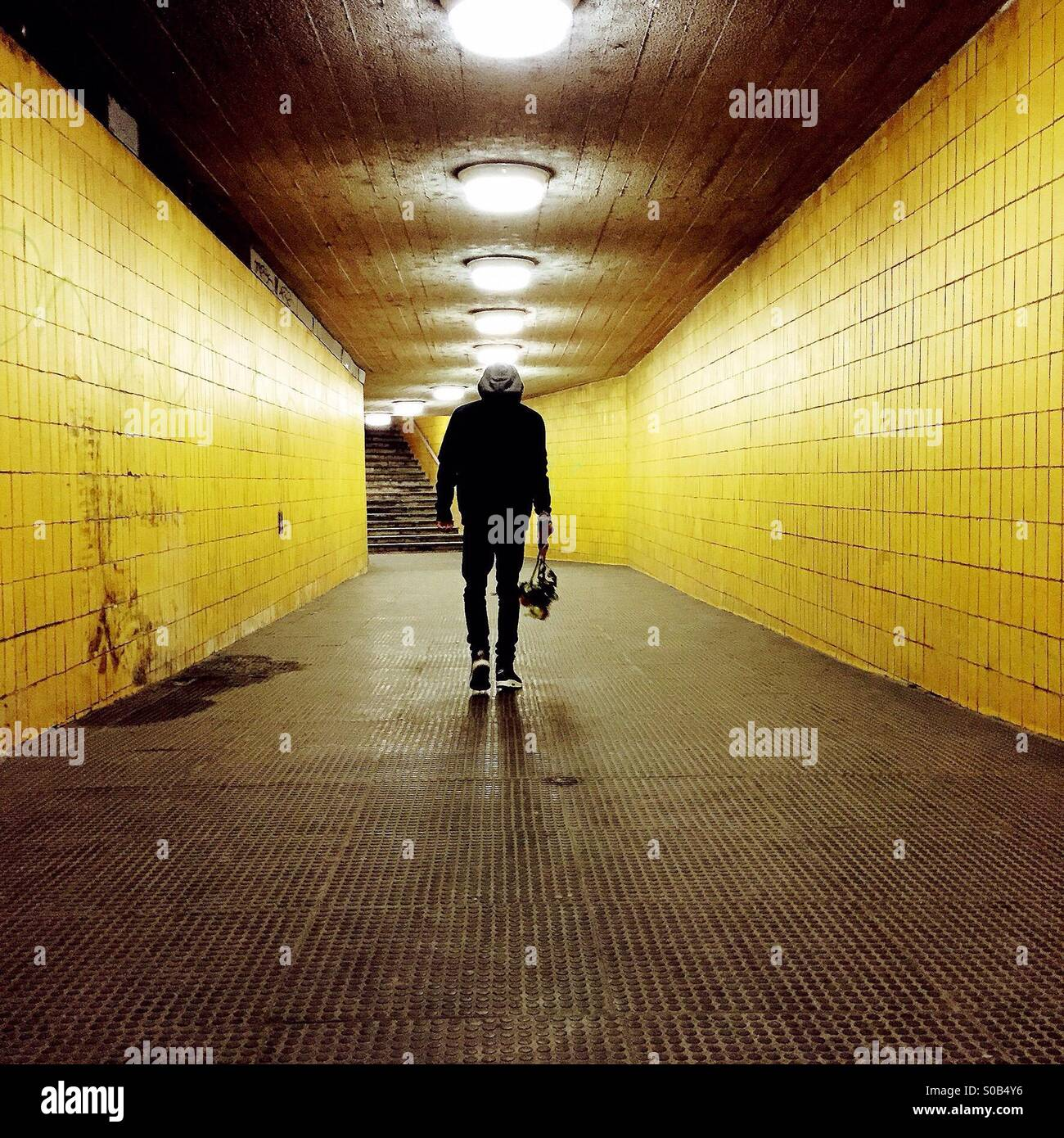 Young man walking under a yellow tunnel - Stock Image