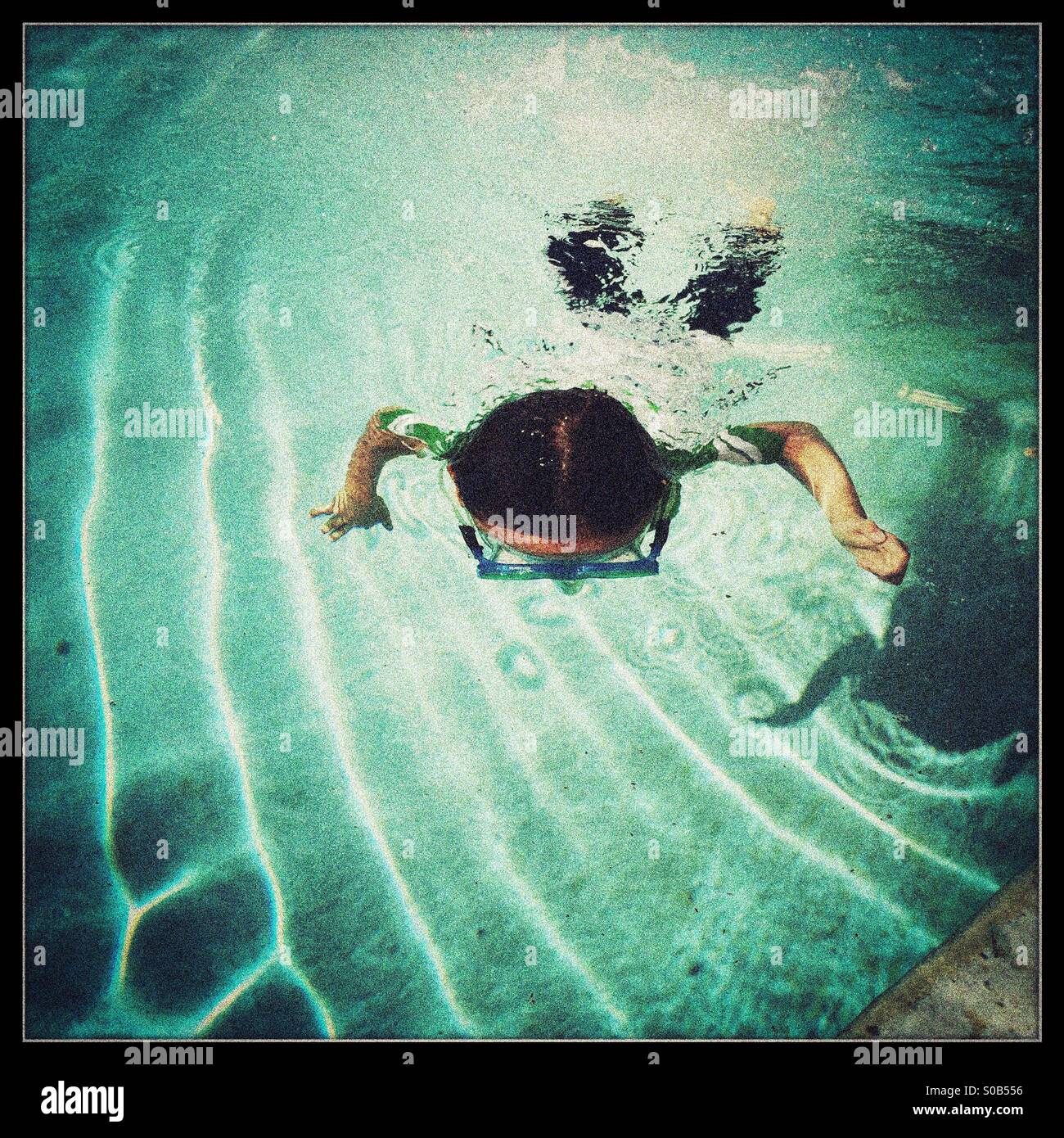 A seven year old boy swims underwater in a swimming pool. - Stock Image