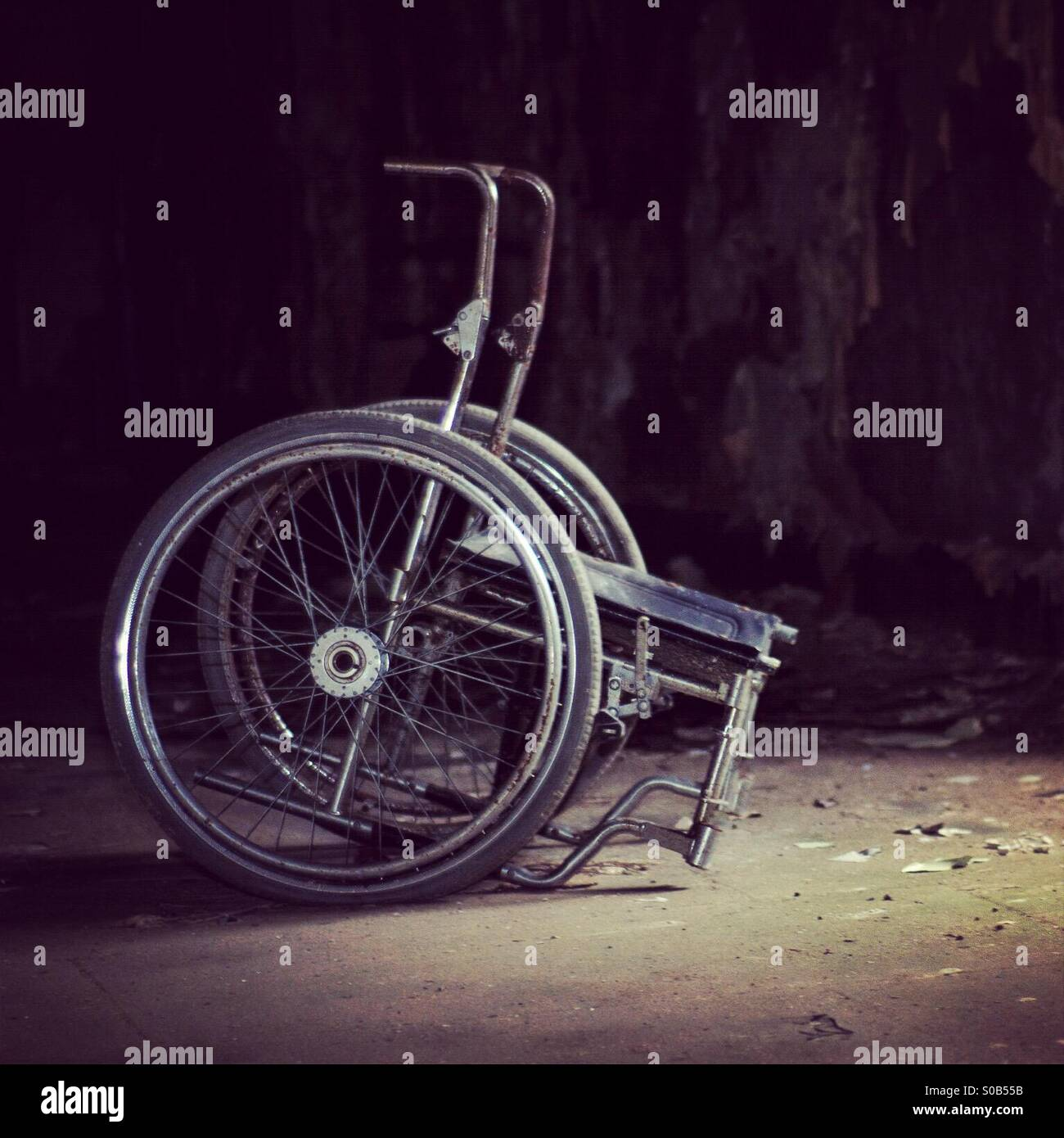 Eerie wheelchair in abandoned building - Stock Image