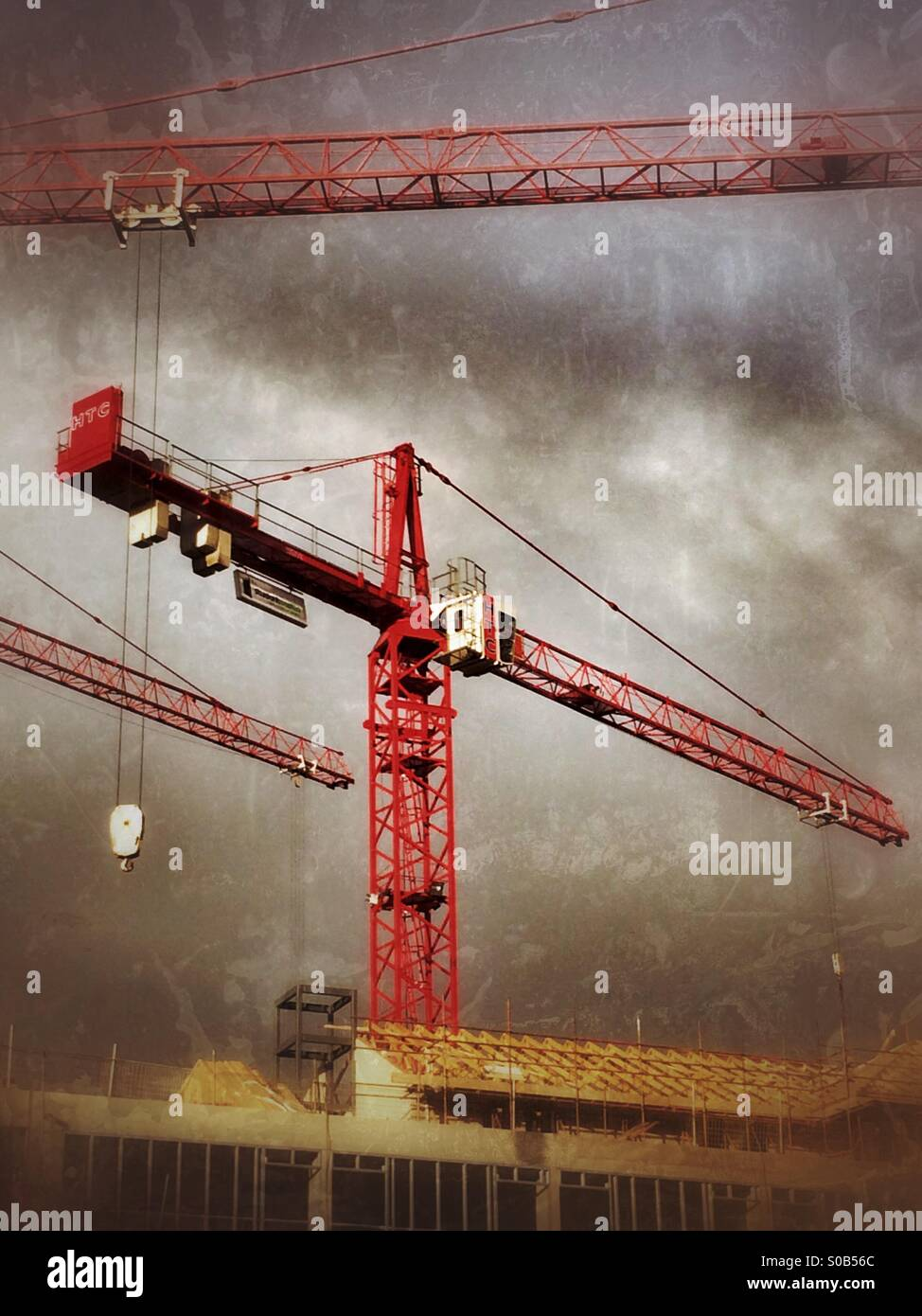 High tower cranes on a building site - Stock Image