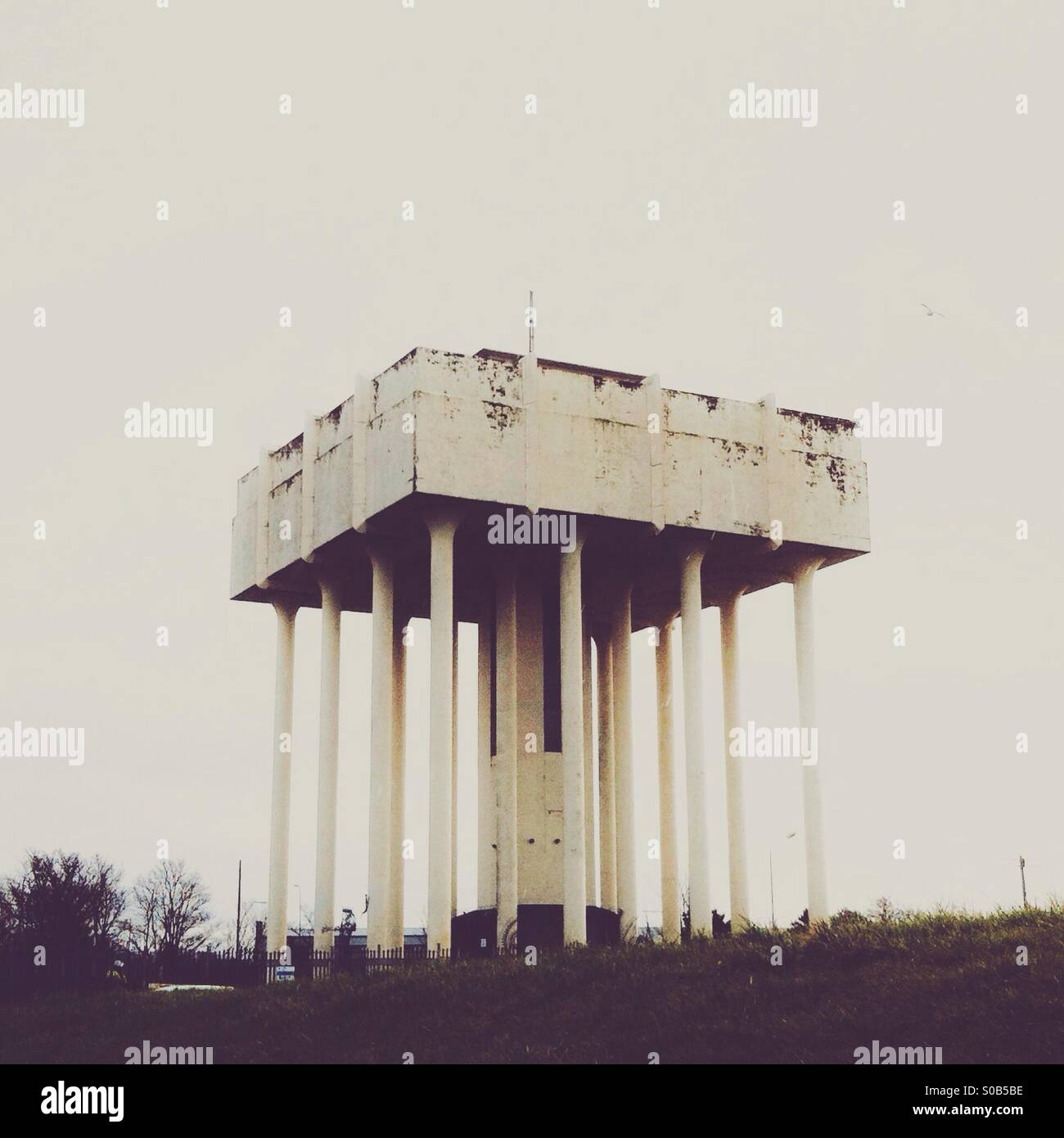 Water tower in muted tones and flat contrast. - Stock Image