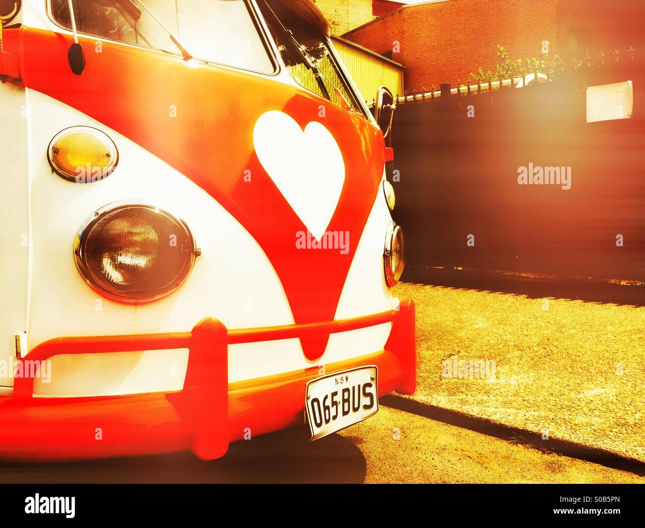 An old VW bus with a heart logo on the front - Stock Image