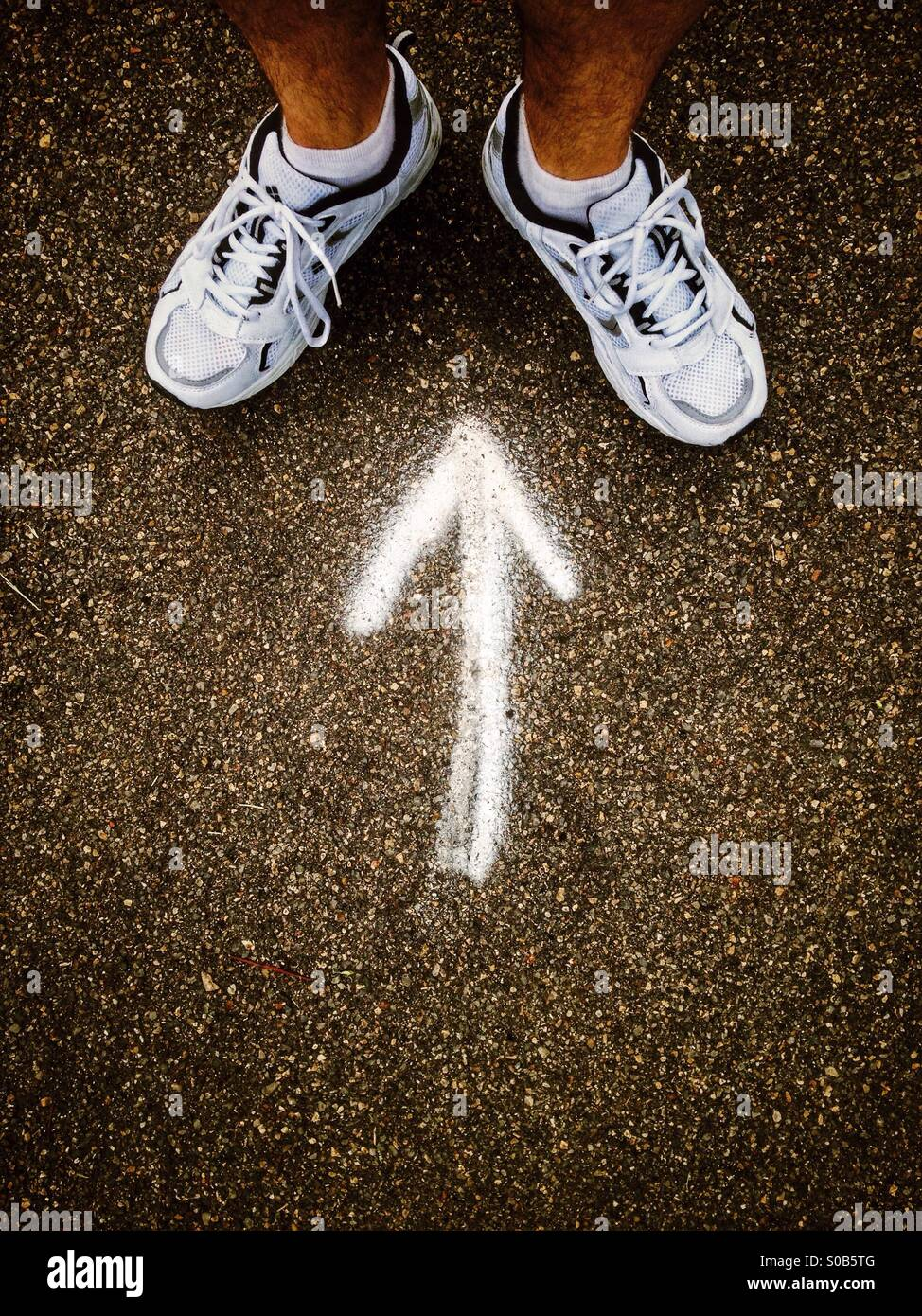 Arrow pointing to a man's feet. - Stock Image