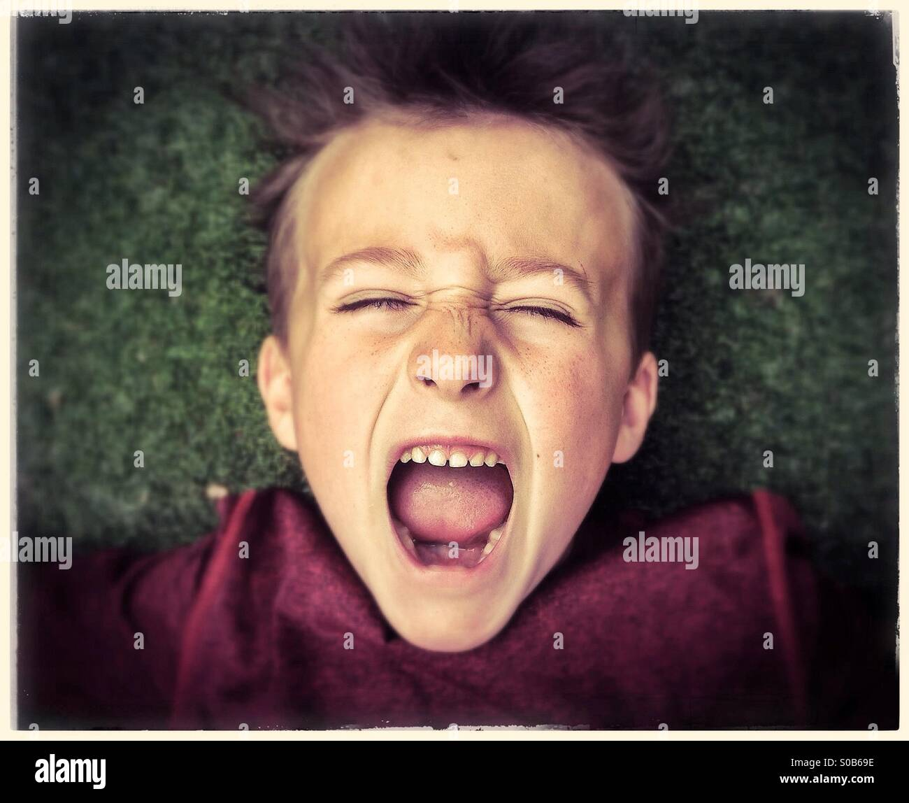Clouse up of a boy, screaming loudly with eyes closed. Boy excited and happy Stock Photo