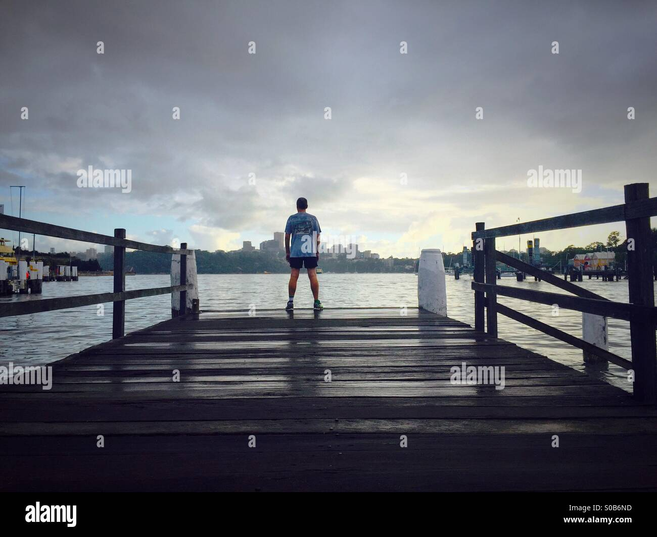 A man in running gear looks out over water - Stock Image